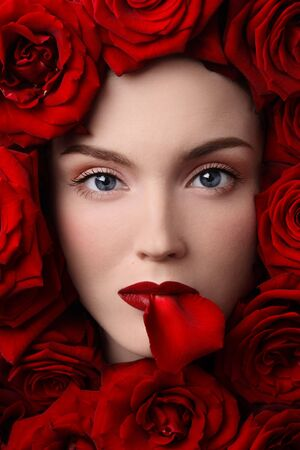 Close-up portrait of pretty young girl in red roses Stock Photo