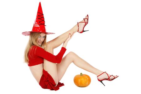 careless: Beautiful blond girl with long legs in costume of Halloween witch sitting on white background Stock Photo