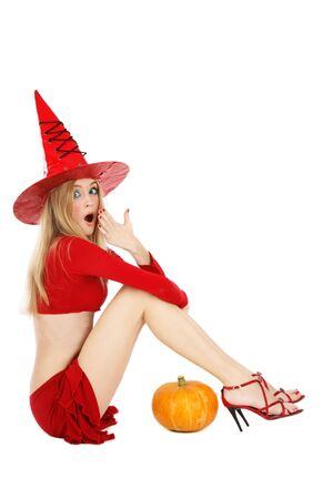 Beautiful blond girl with long legs in costume of Halloween witch sitting on white background with shocked expression Stock Photo - 3711843