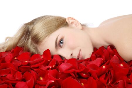 Beautiful blonde girl with clear makeup lying in rose petals Stock Photo