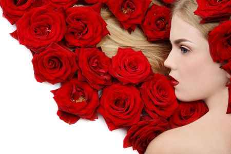 Beautiful girl lying on white background with red roses in her blond hair Stock Photo