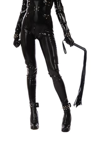 Legs of slim woman in black latex catsuit with cuffs and whip Stock Photo