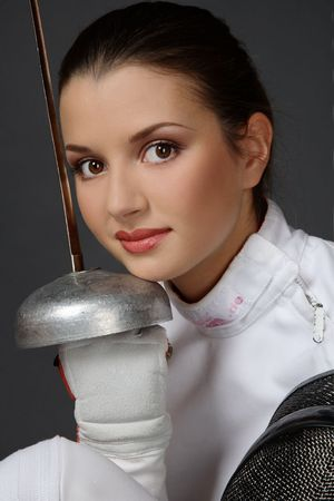 Portrait of young fresh beautiful girl in fence costume with sword and fencing mask photo