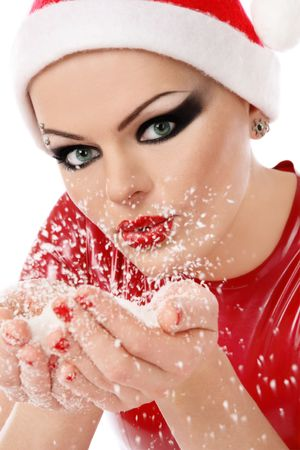 Girl with heavy makeup in Santa hat and latex dress holding snowflakes in cupped hands  photo