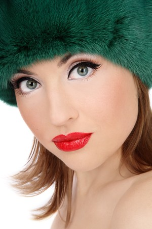 Portrait of beautiful woman with cat eyes in green fur hat photo