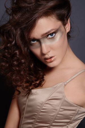 Portrait of beautiful girl with curling hair and creative golden makeup photo