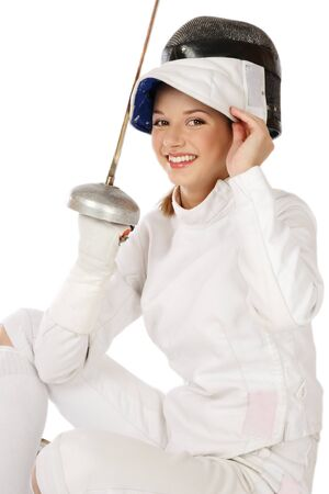 Young fresh beautiful laughing girl in fence costume with sword and fencing mask over white background