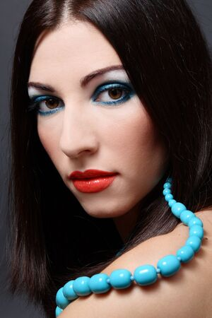 entice: Portrait of beautiful brunette with bright makeup and turquoise beeds Stock Photo