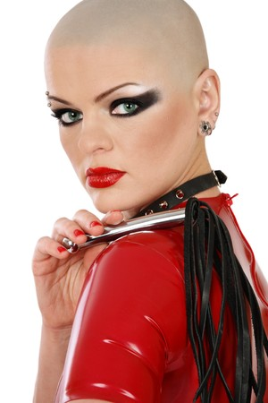 masochism: Portrait of skinhead woman in red latex dress and leather collar with whip in hand, over white background