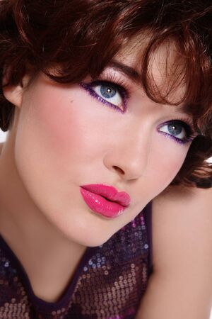 Close-up portrait of beautiful stylish young woman with bright trendy makeup photo