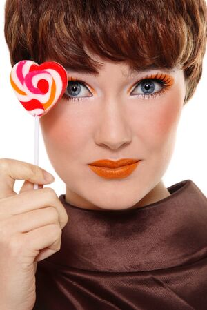 entice: Portrait of beautiful smiling girl with stylish orange makeup and lollipop in hand over white background