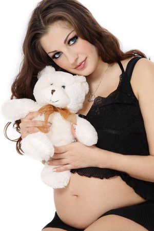 Beautiful pregnant woman in black lingerie holding teddy bear, over white background photo