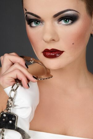 fetishism: Girl in white vinyl dress and gloves holding cuffs Stock Photo