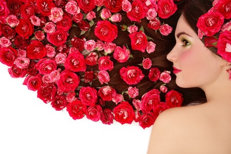 Beautiful girl lying on white background with red roses in her long hair Stock Photo