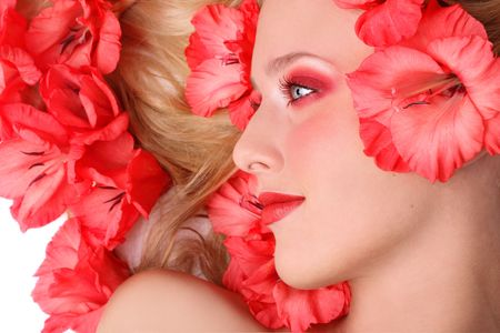 Beautiful girl lying on white background with pink flowers roses in her blond hair photo