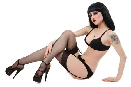 garter belt: y brunette in bra, garter belt, stockings and stilettos sitting on white background Stock Photo