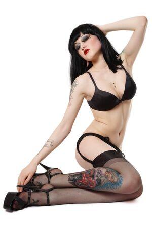 y brunette in bra, garter belt, stockings and stilettos sitting on white background Stock Photo