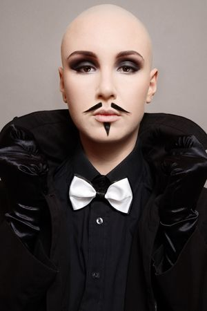 freaks: Skinhead girl in black clothes and false mustache on her face Stock Photo