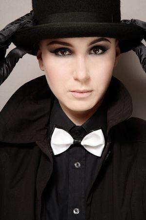 Portrait of skinhead girl with dark makeup holding black hat photo