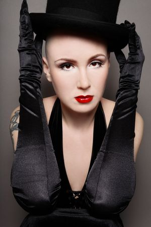 skinhead: Portrait of skinhead woman with glamorous makeup holding black hat