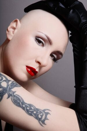 skinhead: Portrait of beautiful skinhead girl with tattoo in long black gloves Stock Photo