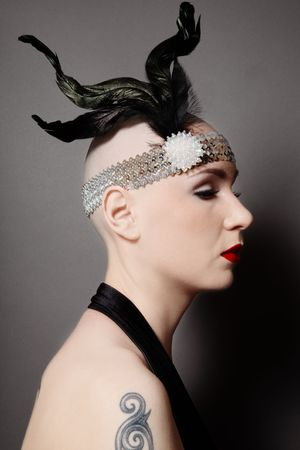 bald girl: Profile of skinhead woman in black dress and stylish plumage