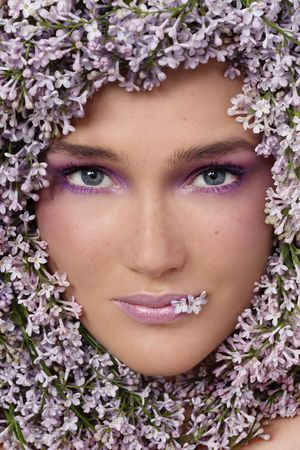 Portrait of beautiful girl with stylish makeup and flowers around her face photo