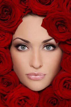 Portrait of beautiful girl with stylish makeup and red roses around her face photo