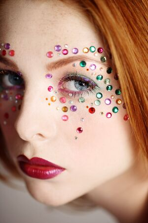 Close-up portrait of beautiful redhead girl with fancy makeup, selective focus photo