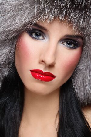 Close-up portrait of beautiful glamorous brunette in stylish fur hat photo