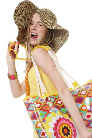 grimacing: Beautiful slim young stylish grimacing girl with yellow sunglasses and bright bag
