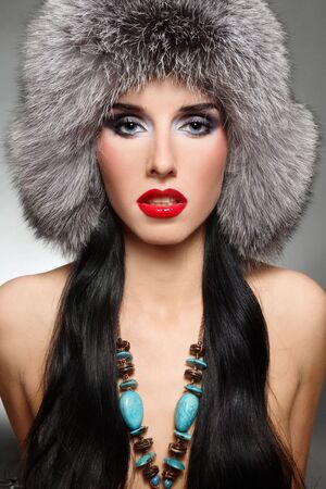 Portrait of beautiful sexy glamorous brunette in stylish fur hat photo