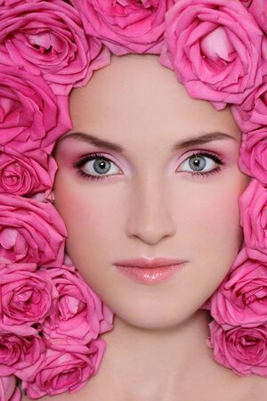 Portrait of beautiful girl with trendy makeup and pink roses around her face photo