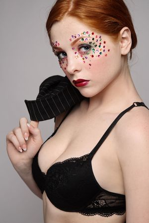 Beautiful redhead girl with fancy makeup in sexy black bra photo
