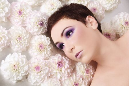 Portrait of beautiful girl with stylish makeup lying on silver background with flowers around her head Stock Photo - 5518650