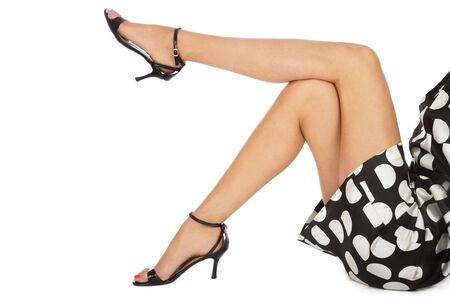Legs of slim tanned woman in stylish peep-toes and polka-dot dress sitting on white background