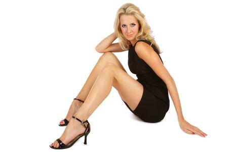 Beautiful slim blonde girl in black cocktail dress sitting on white background  photo