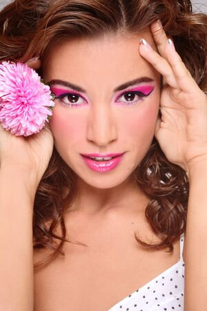 Portrait of beautiful tanned girl with stylish pink makeup and flower in hand photo