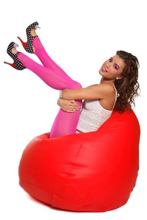 beanbag: Beautiful slim sexy girl in pink pantyhose and stilettos sitting in red bean bag, over white background Stock Photo