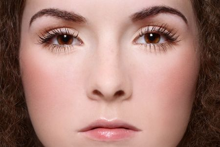 Close-up portrait of young woman face with clear makeup, focus on eyes photo