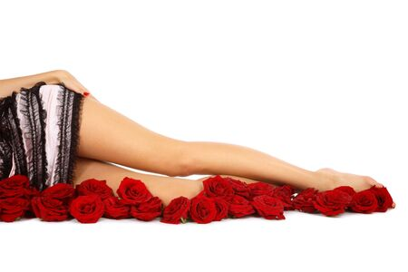 female legs: Legs of slim tanned girl in stylish sexy lingerie lying on white background with roses
