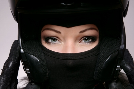 motorbikes: Close-up portrait of beautiful woman with stylish makeup in black biker helmet, mask and gloves