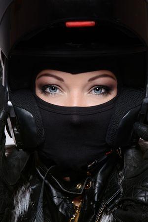 motorrad frau: Portrait der sch�nen Frau mit Make-up im stilvollen schwarzen Biker-Helm, Maske und Handschuhe
