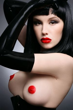 Beautiful sexy brunette in black latex corset and gloves