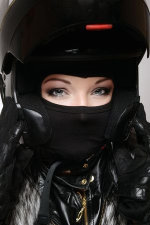 Portrait of beautiful woman with stylish makeup in black biker helmet, mask and gloves photo