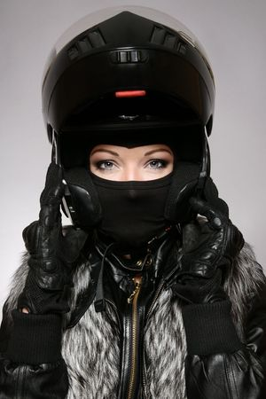 Beautiful woman with stylish makeup in black biker helmet, mask and gloves photo