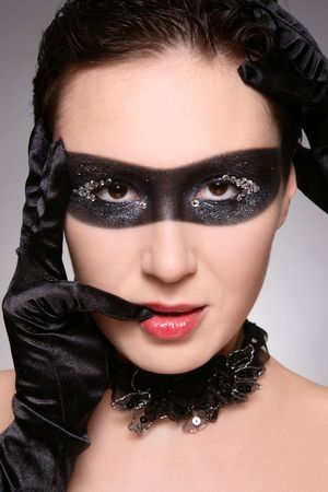 faceart: Portrait of woman in black sparkly mask painted on her face