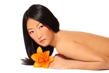 Beautiful young asian girl with bright flower in hand lying on white background Stock Photo - 6474765