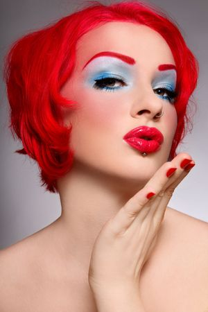 Portrait of young beautiful redhead girl with fancy make-up throwing kiss Stock Photo - 6474772