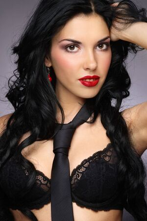 allure: Young beautiful sexy woman in black bra and necktie